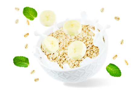 Oat bowl with splash of milk and flying banana slices isolated Stock Photo