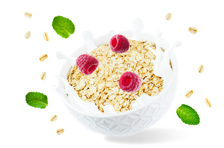 Oat bowl with splash of milk and flying raspberries isolated