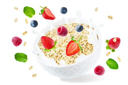 Oat bowl with splash of milk and flying raspberries, blueberries and strawberries isolated Stock Photo