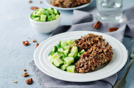 Pecan crust chicken breasts with cucumbers slices on a stone background. toning. selective focus