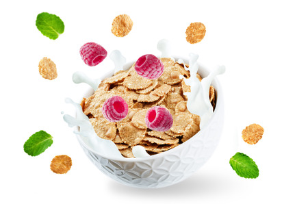 Healthy breakfast with milk, flying whole grain cereals flakes and raspberries isolated