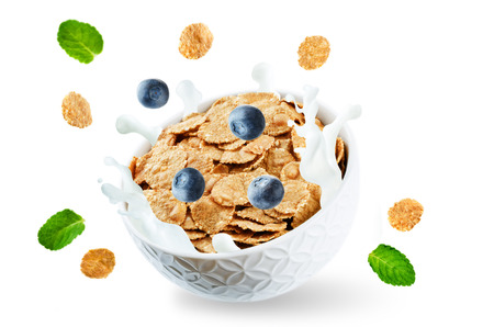 Healthy breakfast with milk, flying whole grain cereals flakes and blueberries isolated Stock Photo