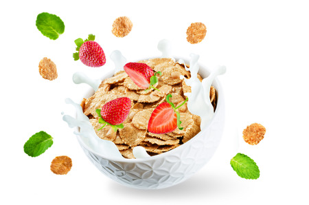 Healthy breakfast with milk, flying whole grain cereals flakes and strawberries isolated