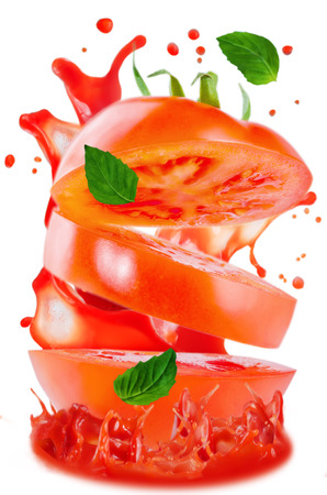 Flying Tomato with splashes of tomato juice and Basil isolated Banco de Imagens