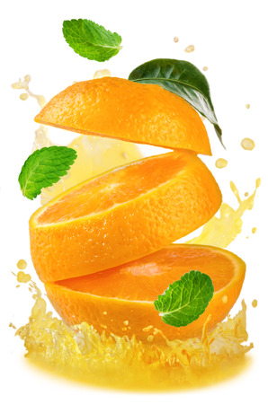 Flying orange with splashes of orange juice and mint isolated