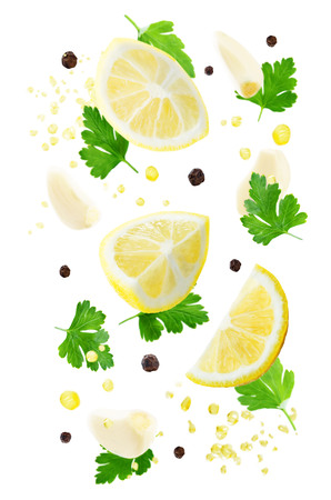 Flying lemons with parsley, garlic and oil spray isolated Stock Photo