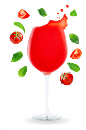 Tomato Juice with flying Tomato slices and Basil leaves isolated