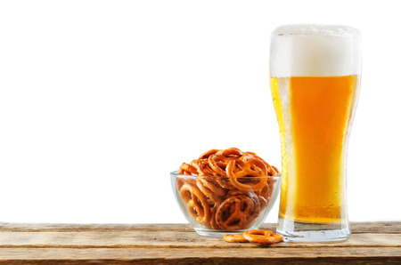 Glass of cold light beer on a wood table isolated