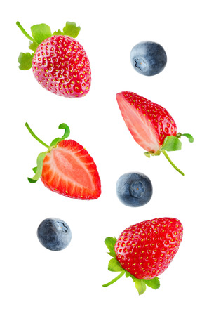 Fresh flying strawberries and blueberries isolated. toning. selective focus Banco de Imagens