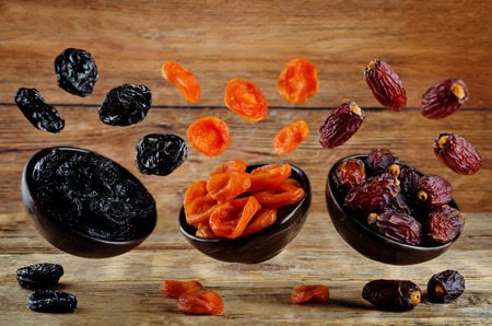 Variation of dried fruits: prunes, dried apricots, dates on a dark wood background. toning. selective focus 版權商用圖片