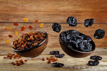 Variation von getrockneten Früchten: Pflaumen und Rosinen auf dunklem Holzhintergrund. Tonen. selektiver Fokus