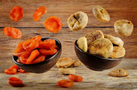 Variation von getrockneten Früchten: getrocknete Aprikosen und getrocknete Feigen auf dunklem Holzhintergrund. Tonen. selektiver Fokus Standard-Bild