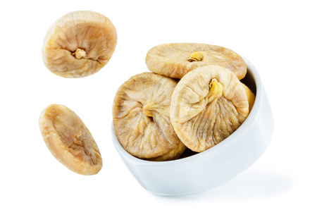 Flying dried Figs fruits in a bowl isolated. toning. selective focus Stock Photo