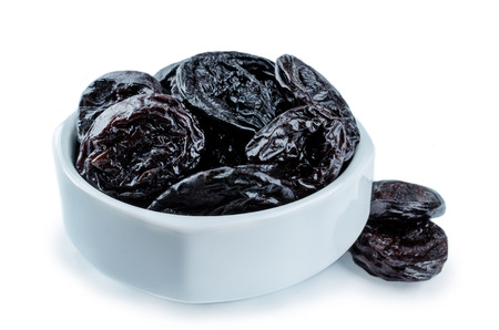 Prugne la frutta in una ciotola isolata. tonificante. messa a fuoco selettiva
