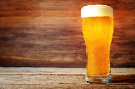 Bicchiere di birra chiara fredda su uno sfondo di legno. tonificante. messa a fuoco selettiva