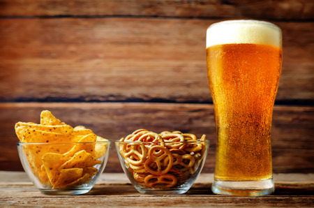 Glass of cold light beer with snacks on a wood  background. toning. selective focus