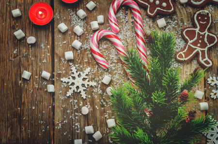 Wood dark background with Christmas tree, candies, cookies, marshmallow and snowflakes. toning. selective focus Reklamní fotografie