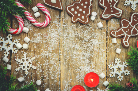 Wood dark background with Christmas tree, candies, cookies, marshmallow and snowflakes. toning. selective focus Stock Photo