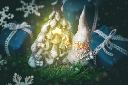Christmas background with toy gnome, gifts and fir tree on a dark background. toning. selective focus Standard-Bild - 110032426