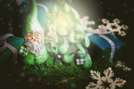 Christmas background with toy gnome, gifts and fir tree on a dark background. toning. selective focus