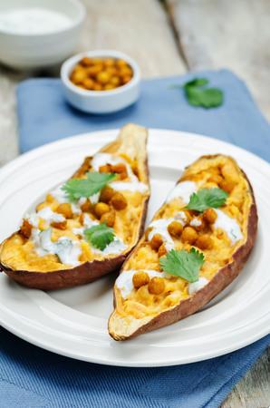 Roasted chickpeas stuffed sweet potato with Greek yogurt cilantro lime dressing. toning. selective focus Standard-Bild - 111011483