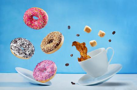 Vliegende kop koffie met veelkleurige donuts