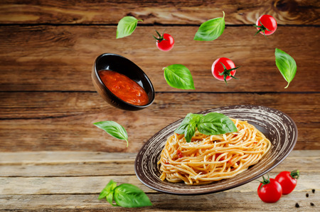 Flying Pasta with Marinara sauce and fresh Basil on a wood