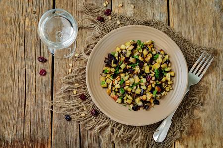 Eggplant pine nuts parsley dried cranberries salad. toning. selective focus
