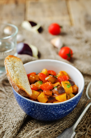 Eggplant potato Bell pepper goulash on a wood background. toning. selective focus