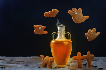Halloween drink in jar with flying cookies on a black background. toning. selective focus