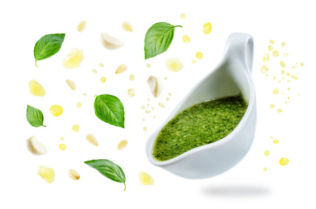 Pesto sauce with flying ingredients to prepare it isolated. toning. selective focus