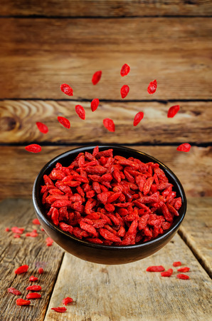 Flying Goji berry in a bowl on a wood background. toning. selective focus Stock fotó