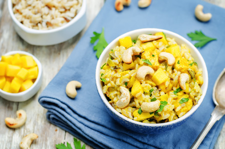 Curry chicken rice with mango and parsley on wood background. toning. selective focus