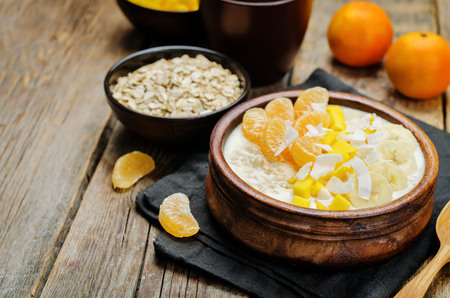 Oatmeal with mango, banana, tangerine oranges and coconut flakes. toning. selective focus 免版税图像
