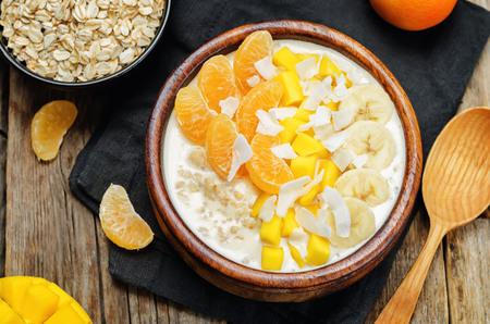 Oatmeal with mango, banana, tangerine oranges and coconut flakes. toning. selective focus Archivio Fotografico