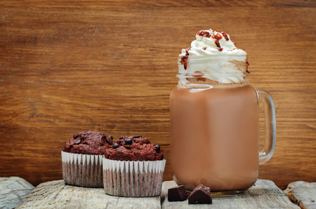 Hot dark chocolate with whipped cream and chocolate cakes. toning. selective focus