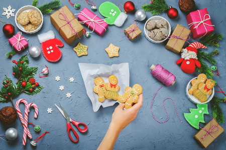 Christmas  with gifts, cookies, Christmas decoration and woman's hands holding cookies Stock Photo - 119753273