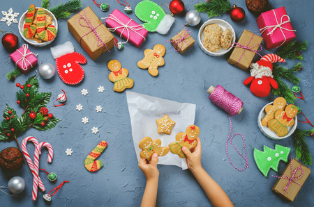 Christmas  with gifts, cookies, Christmas decoration and childrens hands holding ginger bread cookies