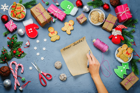Christmas  with gifts, cookies, Christmas decoration and womans hands holding cookies