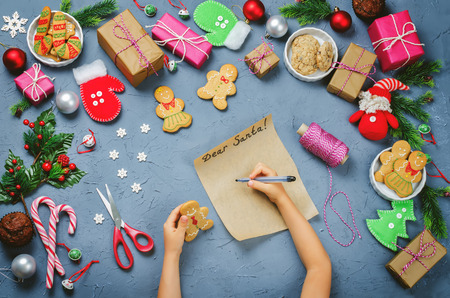 Christmas  with gifts, cookies, Christmas decoration and childrens hands holding gingerbread cookies Stock Photo