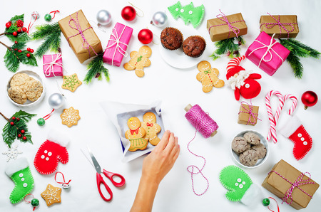 Christmas  with gifts, cookies, Christmas decoration and woman's hands Stock Photo - 119753435