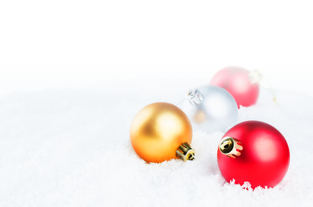 Christmas colored balls on snow isolated