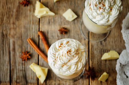 Hot white chocolate with whipped cream and cinnamon on a wood
