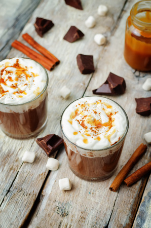 Dark hot chocolate with whipped cream and salted caramel sauce on a wood Фото со стока