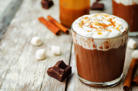 Dark hot chocolate with whipped cream and salted caramel sauce on a wood 写真素材