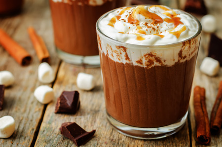 Dark hot chocolate with whipped cream and salted caramel sauce on a wood Imagens