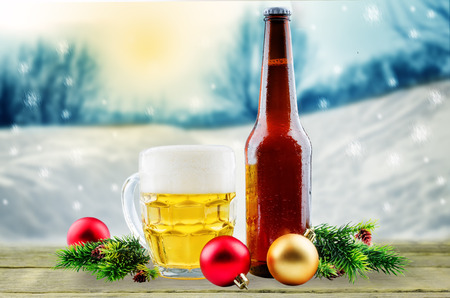 Beer in bottle and in glass with Christmas decoration on a winter background. toning. selective focus