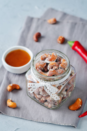 Honey red pepper roasted cashews in a glass. toning. selective focus