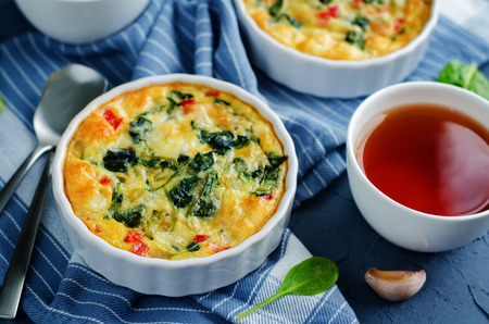 Spinach Red Bell Pepper Baked Omelet with cups of tea and fresh spinach leaves. toning. selective focus