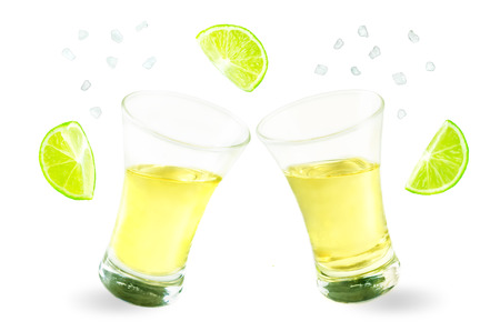 Glass of tequila liquor with falling salt and lime fruits isolated